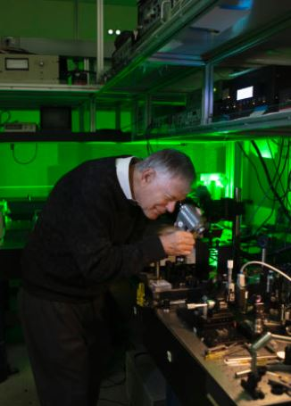 Robert Byer uses an infrared viewing device to check the alignment of a near-IR laser through a linear crystal. Image credit Misha Bruk